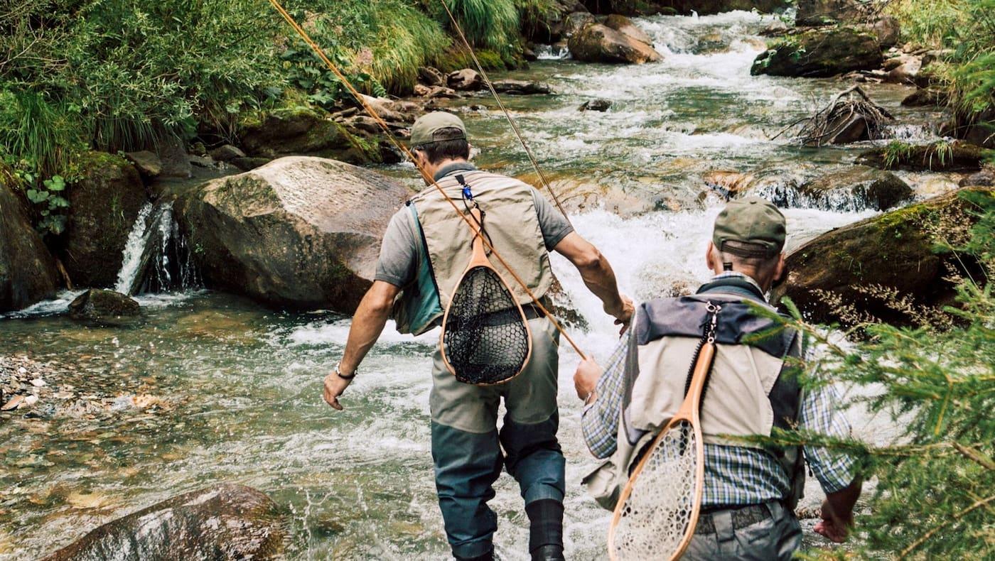 Fliegenfischer wandern durch den Bach