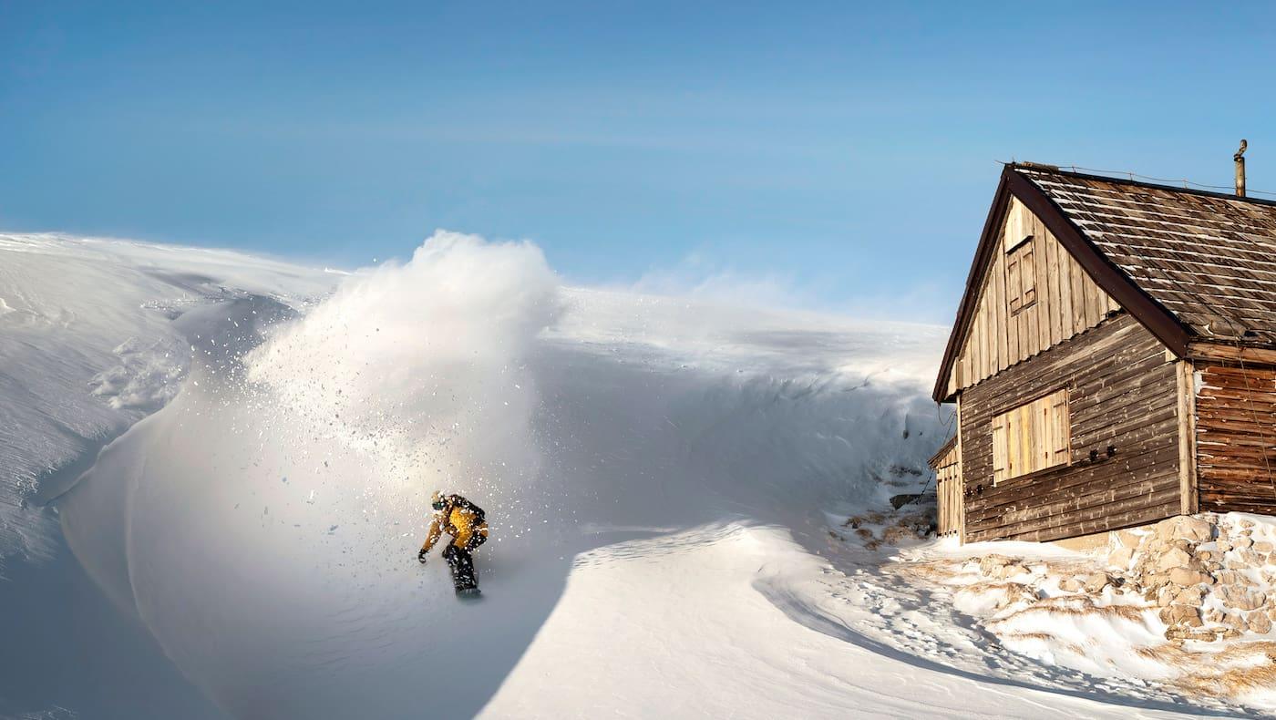 Ein Freerider fährt an einer Hütte vorbei