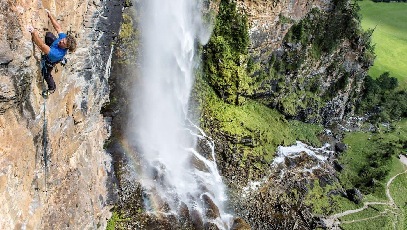 Kletterer klettert gesichert eine Bergwand hoch