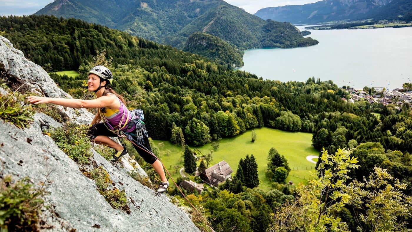 Manuela klettert am Plombergstein, im Hintergrund der türkise Wolfgangsee