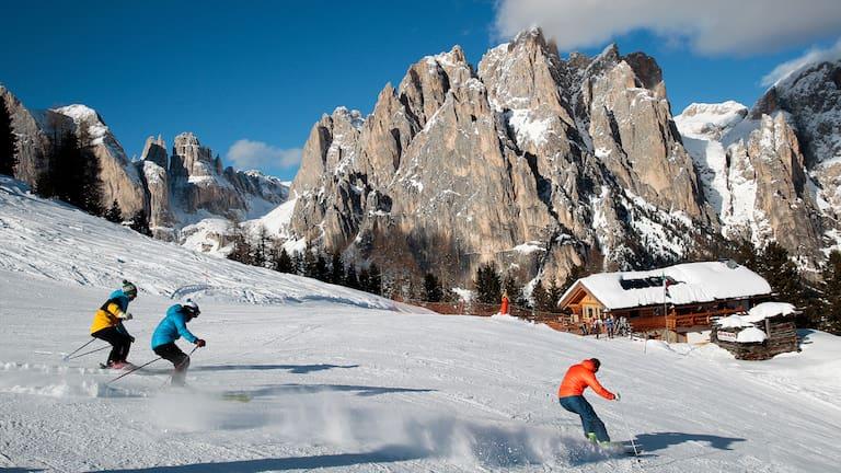 Schwung um Schwung geht es entlang der markanten Gipfel der Dolomiten die Piste hinab.