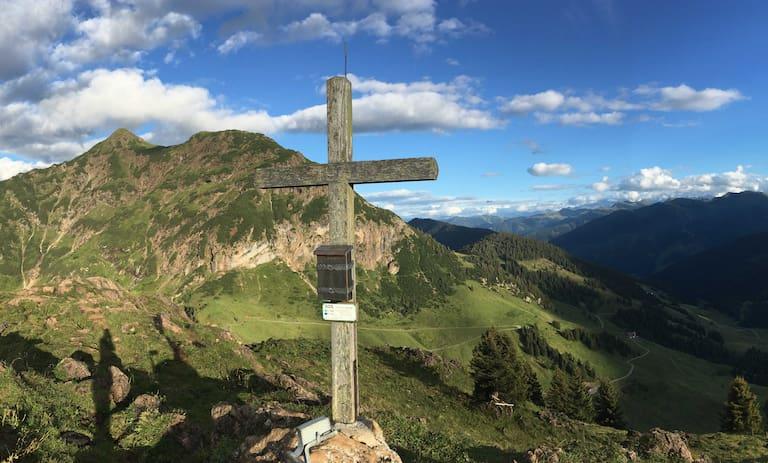 Gipfelkreuz vor Bergpanorama