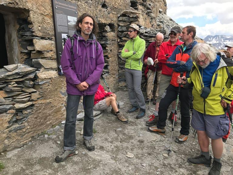 Michael Guggenberger, Archivar des Österreichischen Alpenvereins, erläutert die Geschichte der Salmhütte vor der alten Hütten, die in den Felsen des Schwertecks gesprengt wurde.