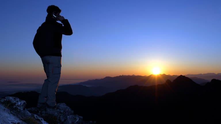 Notfall am Berg: Person im Gebirge am Handy