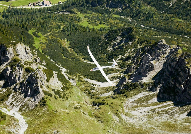 Das Flugzeug ist kaum zu erkennen in den Bergen.