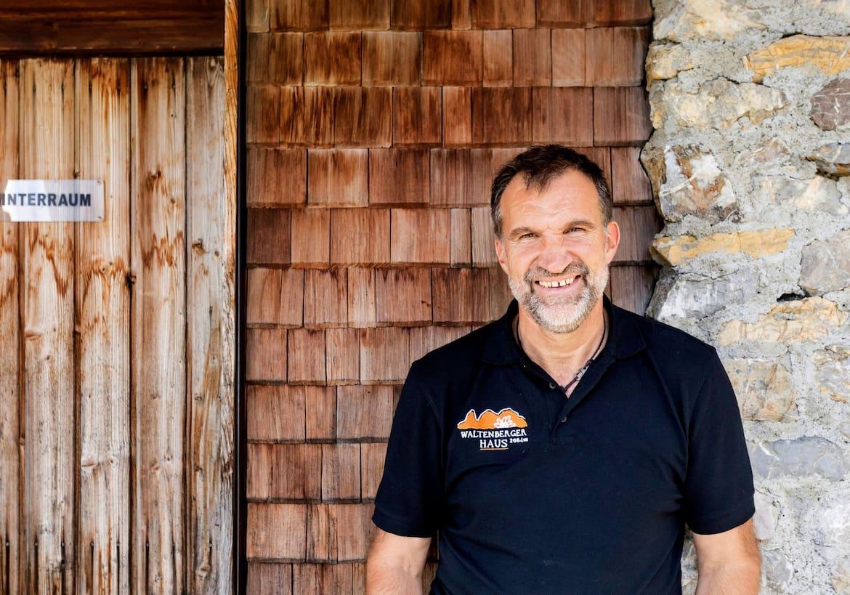 Ein Portrait des Hüttenwirts Markus vor einer Holzschindelwand